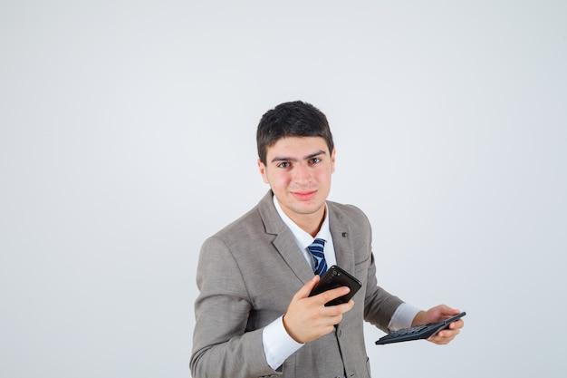 Молодой мальчик в формальном костюме держит телефон и калькулятор и выглядит счастливым, вид спереди.