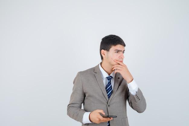電話を持って、あごに手を置いて、何かを考えて物思いにふける、正面図を見てフォーマルなスーツを着た少年。