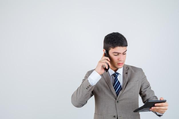 Молодой мальчик в официальном костюме разговаривает по телефону, смотрит на калькулятор и смотрит сосредоточенно, вид спереди.