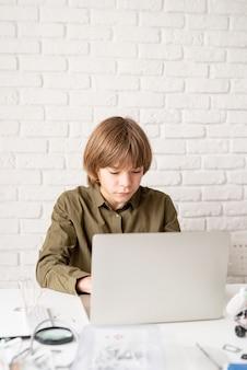 Молодой мальчик в зеленой рубашке работает или учится на ноутбуке дома