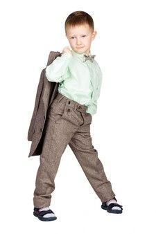 회색 양복과 나비 넥타이에 어린 소년, 반 회전, 그의 재킷을 들고 카메라를 찾고