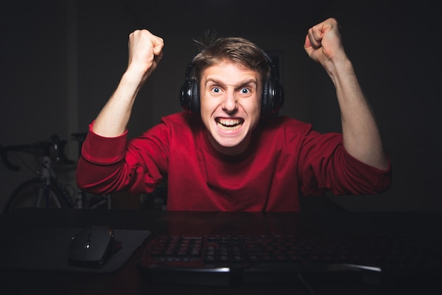 コンピューターと怒っている敗者の自宅でビデオゲームをプレイするヘッドフォンの少年