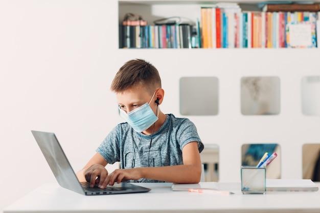 노트북 및 의료 얼굴 마스크와 함께 테이블에 앉아 학교에 준비 헤드셋에 어린 소년