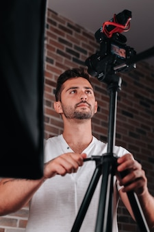 스튜디오에서 카메라 삼각대를 조정하는 20대 소년