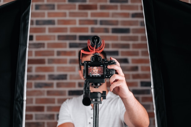 자신의 채널에서 라이브 쇼를 시작하기 위해 카메라를 설정하는 20대 소년
