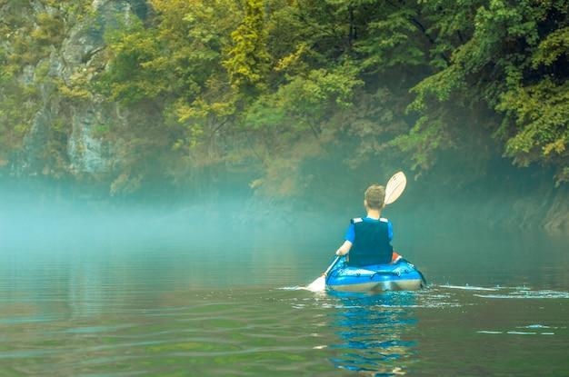 산 호수에 안개에 카약에 어린 소년