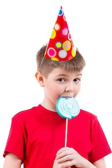 Мальчик в красной футболке и партийной шляпе ест цветные конфеты - изолированные на белом.