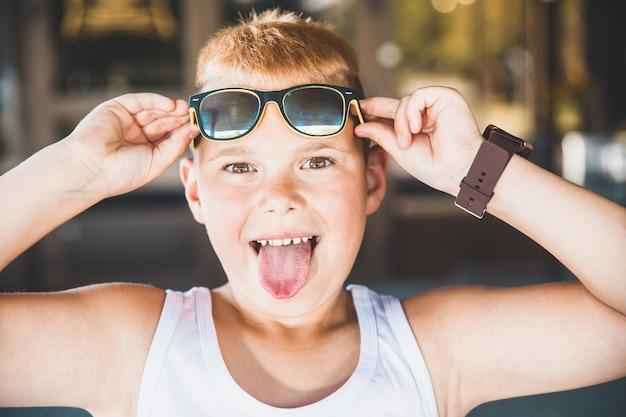 Молодой мальчик в солнечных очках высунул язык.