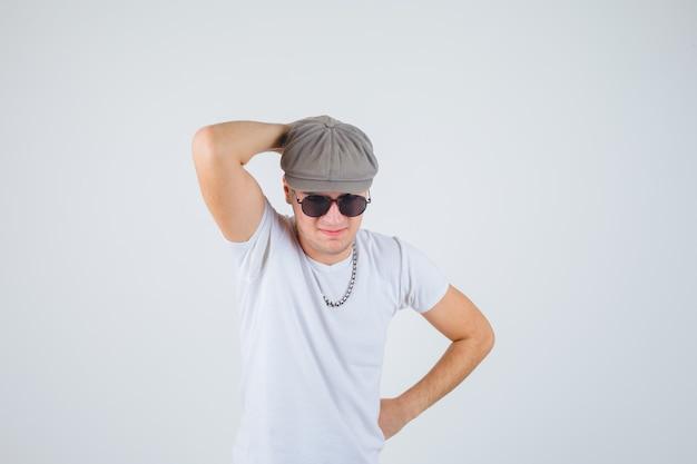 Tシャツを着た少年、頭の後ろに手を握り、思慮深く見える帽子、正面図。