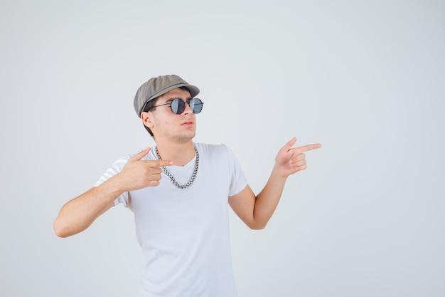 T- 셔츠, 모자 옆으로 가리키고 자신감, 전면보기를 찾고있는 어린 소년.