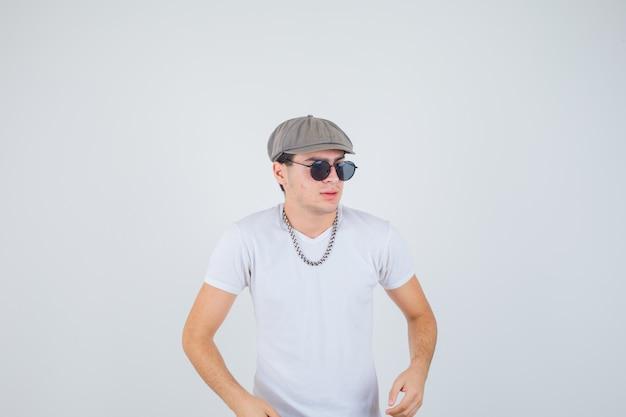 T- 셔츠, 모자 옆으로보고 멋진, 전면보기 동안 포즈 어린 소년.