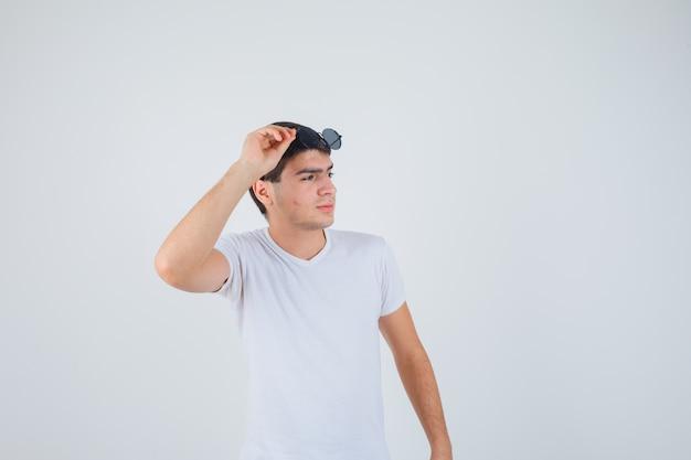 안경을 들고, 옆으로 찾고 잠겨있는, 전면보기를 찾고 t- 셔츠에 어린 소년.