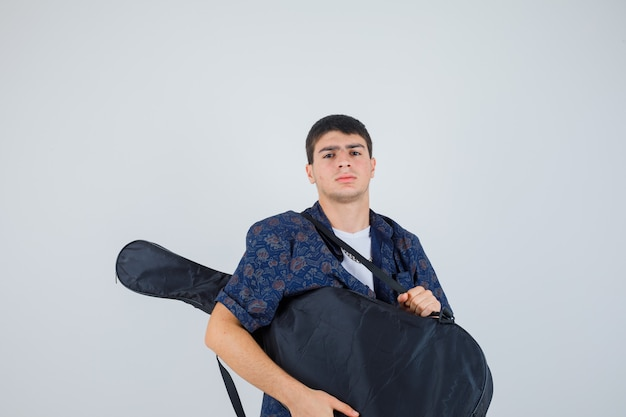 ギターを持って、カメラを見て、真剣に、正面図を見てtシャツを着た少年。