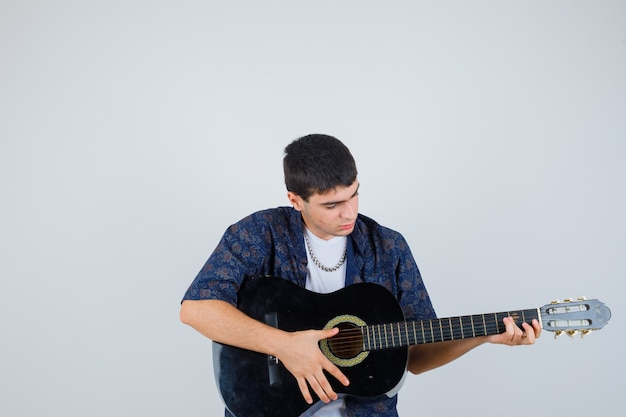 Молодой мальчик в футболке играет на гитарах и выглядит уверенно, вид спереди.