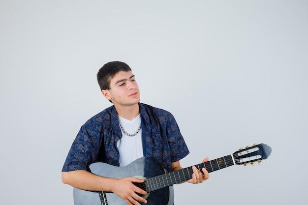 Молодой мальчик в футболке играет на гитарах, глядя в сторону и выглядит довольным, вид спереди.