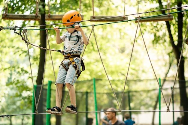 ロープパークの少年。公園での子供のアクティブな残り。