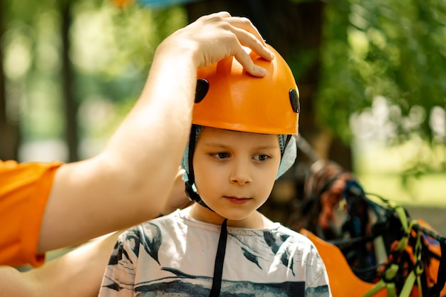 ロープパークの少年。保護用のヘルメットをかぶる。