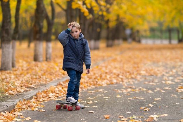 スケートボードで額に手をかざして、あたかも傷ついたかのように、公園で一人で立っている暖かいジャケットを着た少年。黄色の葉と木