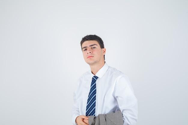 흰 셔츠에 어린 소년, 포즈와 화려한, 전면보기를 찾고있는 동안 팔에 재킷을 들고 넥타이.