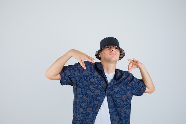 Молодой мальчик в белой футболке, рубашке с цветочным рисунком, кепке показывает знак ок, делает жесты руками и выглядит уверенно, вид спереди.