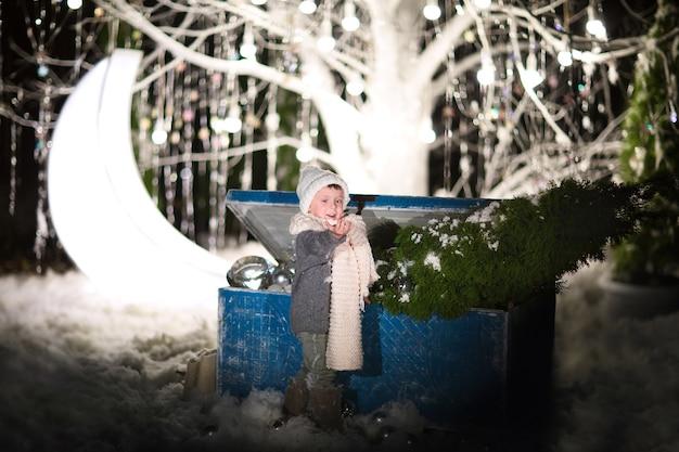 古い青の近くでクリスマスのおもちゃでポーズをとる冬の帽子、セーター、スカーフの少年