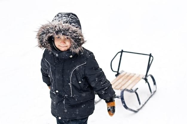 そりを引いて冬スーツの少年