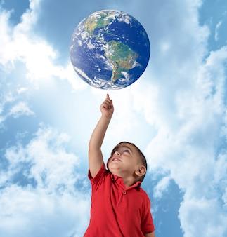 少年は青い空に世界を示しています。