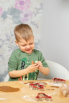A young boy is getting ready for christmas. press the shapes of gingerbread.