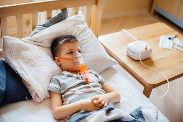 A young boy is given an inhalation during a lung disease. medicine and care.