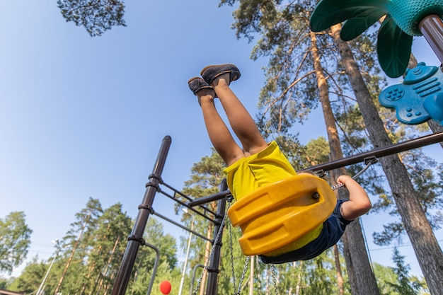 A young boy is having fun on a swing on the playground trying to touch the sky with his legs