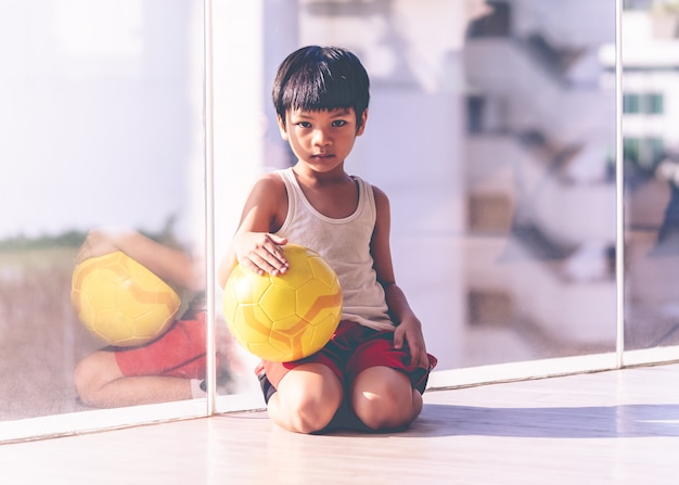 Young boy is sitting with soccer on the floor