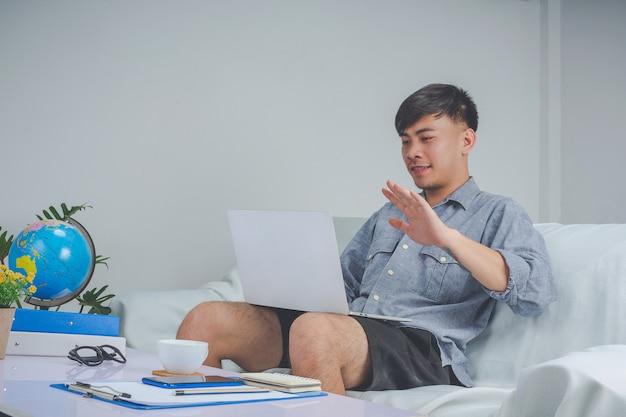 若い男の子はlabtopで働いていて、自宅のソファーでの作業に忙しい。