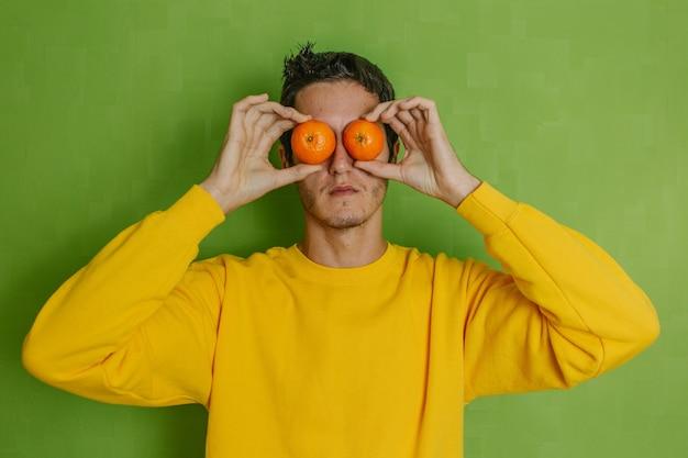 Молодой мальчик шутит с двумя апельсинами в глазах на зеленом фоне