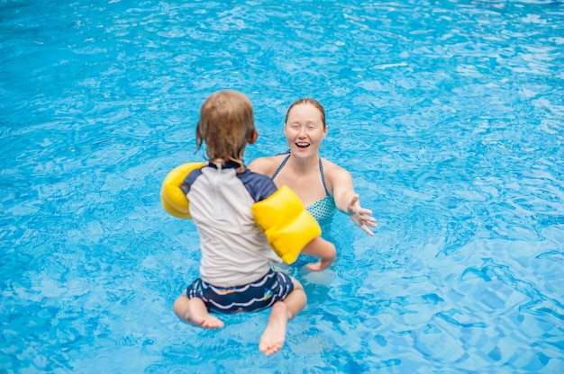 Young boy jump into the water of swimming pool