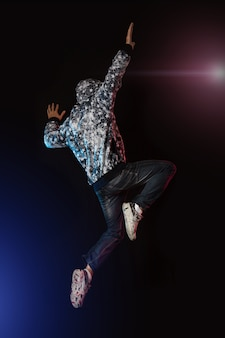 Young boy jumping on black wall