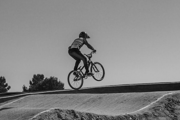 Молодой мальчик прыгает на велосипеде bmx в черно-белом цвете на трассе.