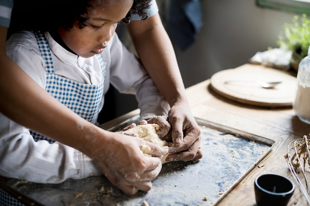 Young boy leaning to bake with his mother