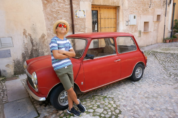 Young boy leaning on red car on narrow street