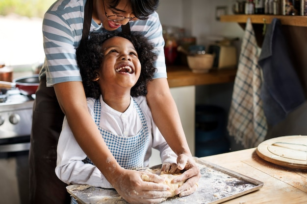 Young boy learning to bake with his mother