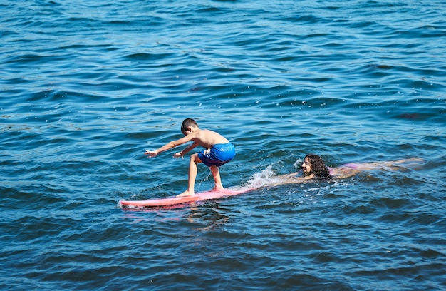 Young boy learning to surf with her older sister