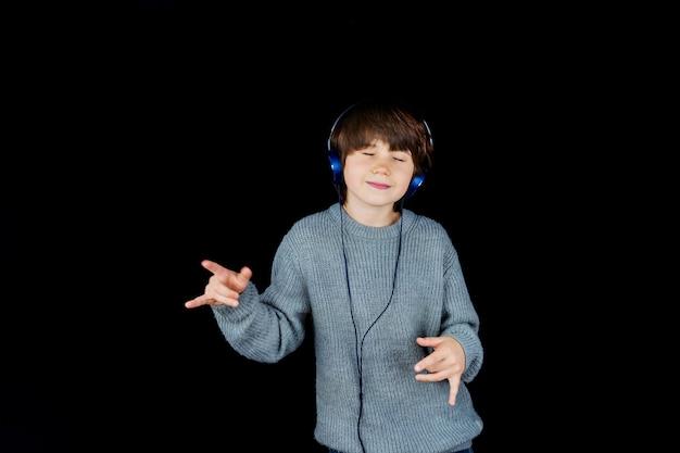 Молодой мальчик слушает музыку на плеере с наушниками на черном