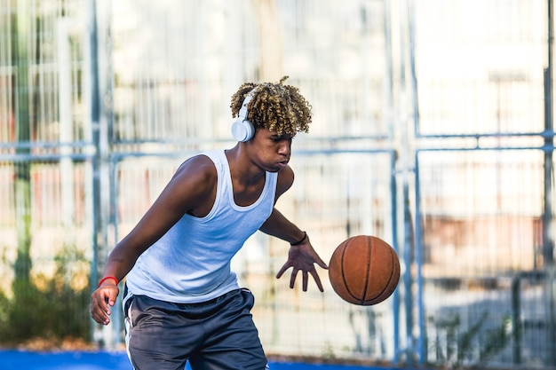 A young boy listens music in his headphones while playing basketball with a ball on the court