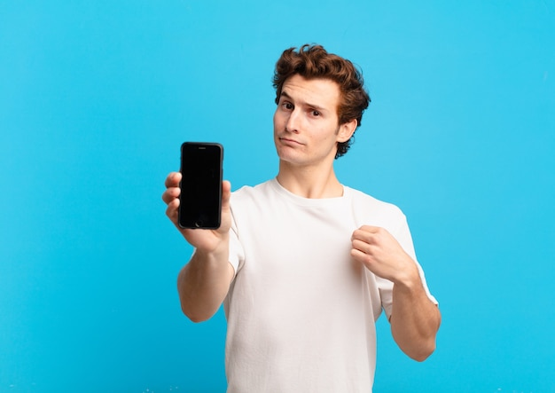 Young boy looking arrogant, successful, positive and proud, pointing to self. telephone screen concept