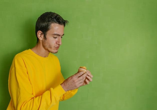 Молодой мальчик смотрит на укушенный кекс, который он держит в руке, зеленый фон