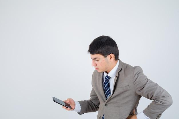 전화를보고, 공식적인 양복 엉덩이에 손을 잡고 집중 찾고 어린 소년. 전면보기.