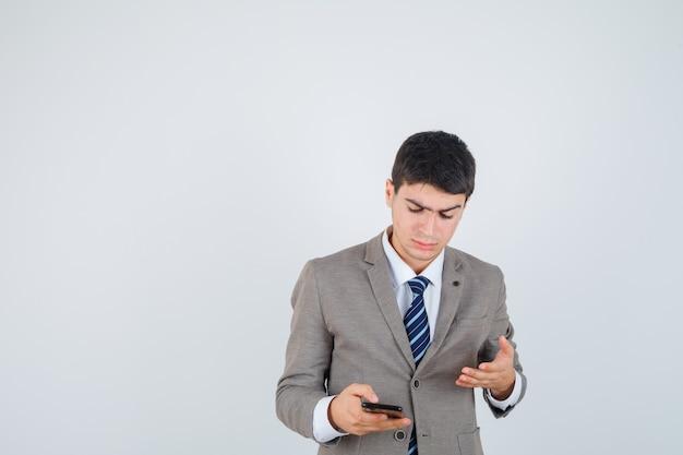 어린 소년 전화를보고, 공식적인 소송에서 그것을 향해 손을 뻗어 초점을 맞춘, 전면보기를 찾고.