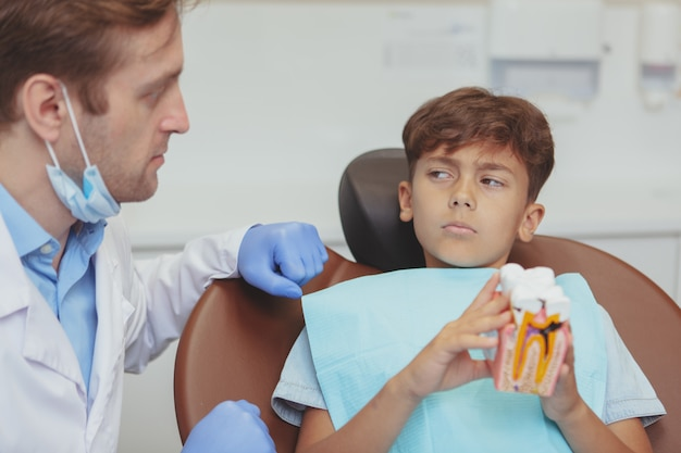 Young boy looking at the dentist suspiciously, preparing for his caries dental treatment at the clinic