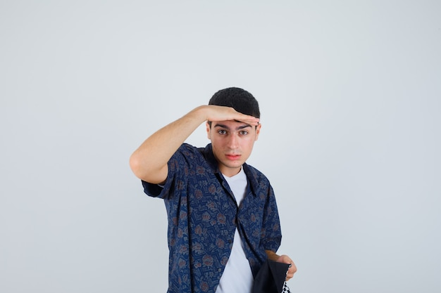Young boy looking far away with hand over head, holding cap in white t-shirt, floral shirt, cap and looking focused.