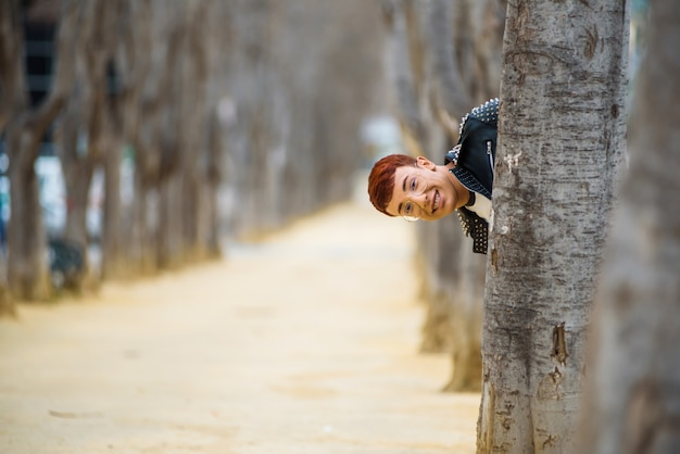 Young boy looking out of the tree in a park