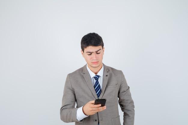 Ragazzo che guarda al telefono in abito formale e guardando concentrato. vista frontale.